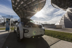 A BMW i3 plug-in automobile, produced by Bayerische Motoren Werke AG , sits beside an electric charging station outside the BMW World showroom in Munich, Germany, on Tuesday, Jan. 26, 2016. BMW is at risk of losing its lead in the luxury car market this year to Mercedes-Benz after reporting the slowest sales growth since 2009 while its German arch-rival charged ahead with a fresher lineup and surging demand in China. Photographer: Martin Leissl/Bloomberg