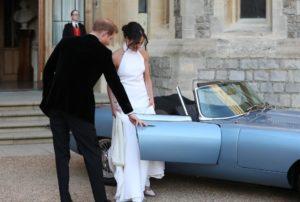 """Дворецът Кенсингтън: Херцогинята и херцогът на Съсекс отпътуват от замъка Уиндзор за прием, организиран от принца на Уелс във """"Фрогмор Хаус"""", в сребристо синьо концептуално нулево Jaguar E-Type. Превозното средство първоначално е произведено през 1968 г. и е преобразувано в електрическо."""