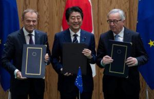Японският премиер Шино Абе стои заедно с председателя на Европейската комисия Жан-Клод Юнкер и президента на Европейския съвет Доналд Туск със знамената на ЕС и Япония зад тях.
