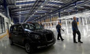 Работниците минават покрай електрическо такси в завода на London Electric Vehicle Company