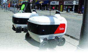 Два Yandex Rover очакват следващата си мисия за доставка извън Amer's Deli в Ан Арбър, Мичиган. Руската технологична компания се стреми да добави към списъка си с местни предложения за доставка на храна до есента.