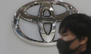Мъж с маска за лице минава покрай логото на Toyota Motor Corp. в нейния шоурум в Токио