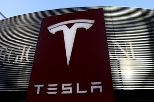 FILE PHOTO: Logo of the electric vehicle maker Tesla is seen near a shopping complex in Beijing