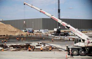 Работниците работят с машини на строителната площадка на фабриката на Tesla в Груенхайде, близо до Берлин, на 12 август 2021 г.